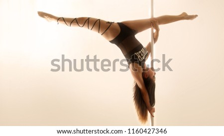 AGUASCALIENTES - MAR 3, 2018: Pole dancer making a complex pose as part of her morning training #1160427346