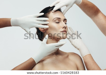 Two cosmetologists touching and examining facial skin of a female. Woman face being checked beauticians hands in studio. #1160428183