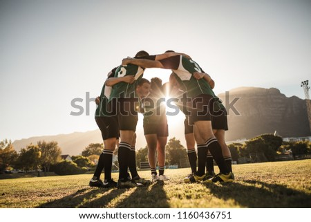 Rugby players standing in a circle with their hands on shoulders. Rugby team in huddle after the match. Bright sunshine through the huddle. #1160436751