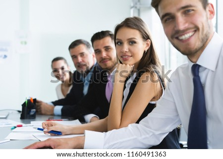 Portrait Of Happy Businesspeople Looking At Camera Sitting In A Row At Office #1160491363
