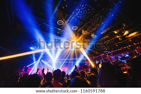 silhouette of concert crowd in front of bright stage lights. Dark background, smoke, concert  spotlights, disco ball Royalty-Free Stock Photo #1160591788