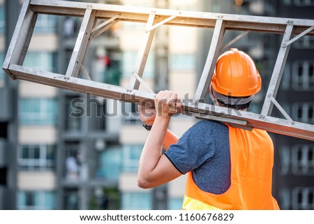 Young Asian maintenance worker man with orange safety helmet and vest carrying aluminium step ladder at construction site. Civil engineering, Architecture builder and building service concepts #1160676829