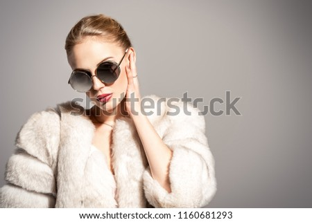 Gorgeous blonde woman posing in luxurious fur coat and sunglasses. Fashion, beauty. Studio shot. #1160681293