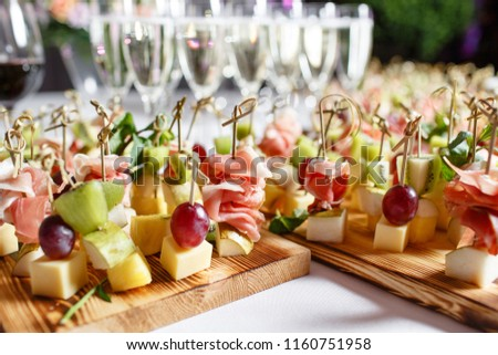 solemn happy new year banquet. Lot of glasses champagne or wine on the table in restaurant. buffet table with lots of delicious snacks. canapes, bruschetta, and little desserts on wooden plate board #1160751958