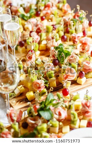 solemn happy new year banquet. Lot of glasses champagne or wine on the table in restaurant. buffet table with lots of delicious snacks. canapes, bruschetta, and little desserts on wooden plate board #1160751973