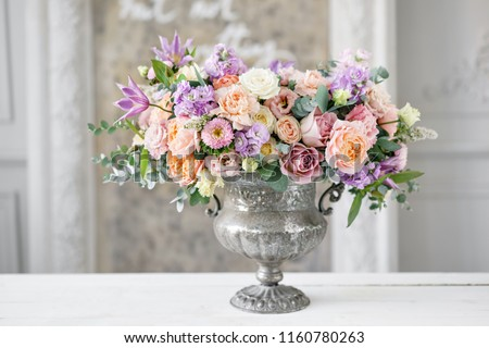 Gorgeous bouquet of different flowers. floral arrangement in vintage metal vase. table setting. lilac and peach color Royalty-Free Stock Photo #1160780263