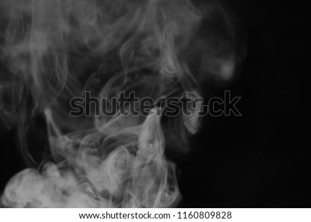 White smoke on a black background. Texture of smoke. Clubs of white smoke on a dark background for overlay #1160809828