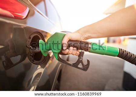 Closeup of man pumping gasoline fuel in car at gas station. Gas pump nozzle in the fuel tank of a gray car Royalty-Free Stock Photo #1160839969