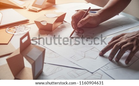 Designer sketching drawing design Brown craft cardboard paper product eco packaging mockup box development template package branding Label . designer studio concept . Royalty-Free Stock Photo #1160904631