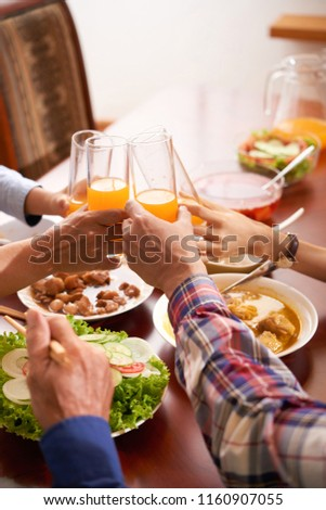 Hands of family memebers clinking glasses of orange juice over dinner table #1160907055