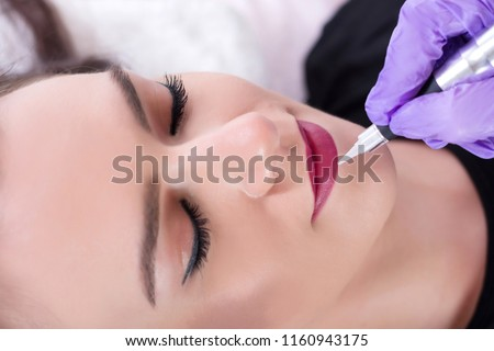 Beautiful young girl getting tattoo red lips in beauty studio. Professional cosmetologist making permanent make up with tool in purple gloves. Close up, selective focus #1160943175