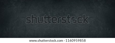 Black rough concrete wall wide texture. Fine textured cement plaster surface with small cracks. Dark gray grunge background #1160959858