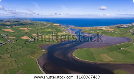 panoramic aerial view surrounding farmland and river flowing into the Atlantic ocean on the west coast of Ireland   #1160967469