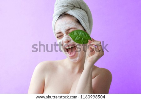 Beauty portrait of a smiling brunette woman in a towel on the head with white nourishing mask or creme on face and green leaf in hand on purple background isolated. Skincare cleansing eco organic #1160998504