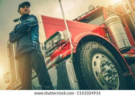 American Trucker Job. Caucasian Truck Driver in Front of His Red Semi Truck. #1161024916