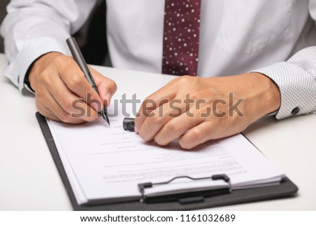 A person signing paperwork #1161032689