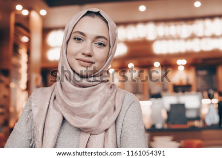 beautiful Muslim girl in hijab smiling, waiting for her food in a restaurant Royalty-Free Stock Photo #1161054391