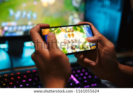 Hands of young gamer boy playing video games on smartphone and computer in dark room wearing headphones and using backlit colorful keyboard #1161055624