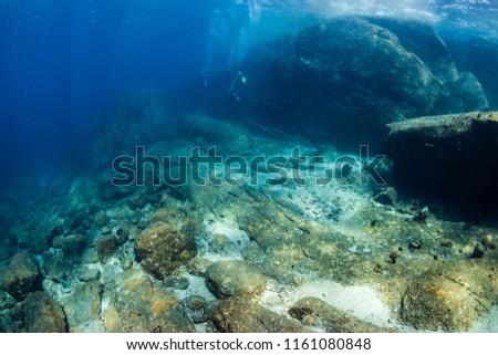 SCUBA divers exploring beautiful underwater scenery in a clear, tropical ocean #1161080848