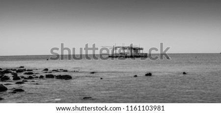 Quiet background with the calm Ocean and fishing boat in the middle in black and white. #1161103981
