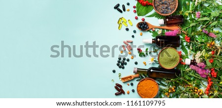 Holistic medicine approach. Healthy food eating, dietary supplements, healing herbs and flowers. Turmeric, dried lavender, spirulina powder in wooden bowls, fresh berries, omega acid capsules. #1161109795