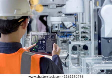 Industry 4.0 Robot concept .Engineers use laptop computers for machine maintenance, automation tools, robot arm at the factory. #1161152758