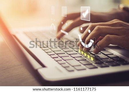 Businesswoman pressing face emoticon on the keyboard laptop / Customer service evaluation concept.  Royalty-Free Stock Photo #1161177175