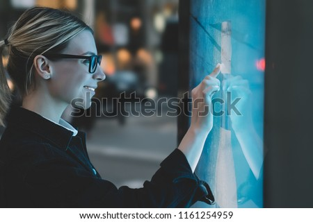 Smiling female standing at big display with advanced digital technology. Young woman touching with finger sensitive screen of interactive kiosk for find information while standing on street in evening #1161254959