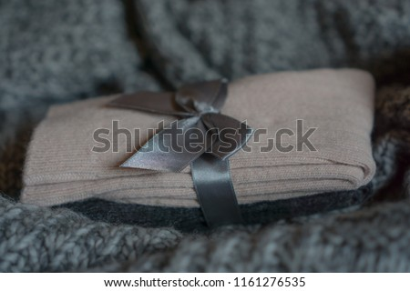 Close-up on a pack of comfy pink grey socks made from wool and cashmere blend located on a knitted plaid. Cozy autumn winter background. Shallow depth of field.  #1161276535