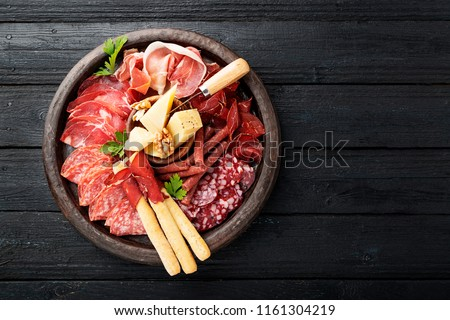Antipasto platter cold meat with breadsticks, prosciutto, slices ham, beef jerky, salami and cheese platter on wooden board over rustic background.  #1161304219