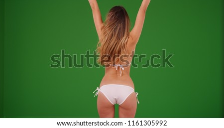 Rear view of Caucasian woman in white bikini celebrating on green screen