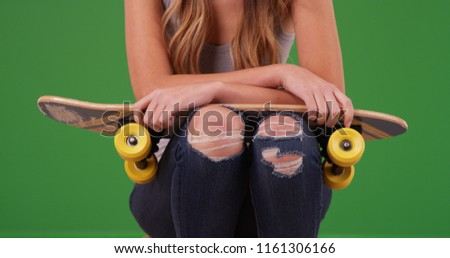 Young white female wearing ripped jeans with skateboard on green screen