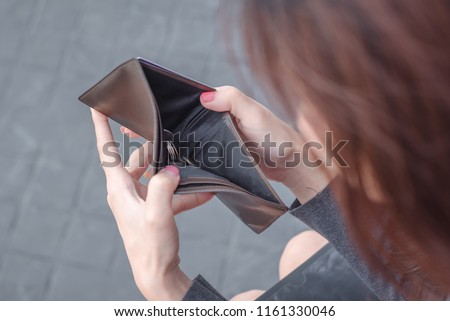 Unhappy bankrupt woman with empty wallet . Young woman shows her empty wallet. Bankruptcy Royalty-Free Stock Photo #1161330046