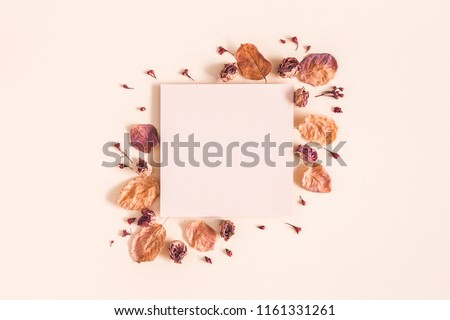 Autumn composition. Paper blank, dried flowers and leaves on pastel beige background. Autumn, fall concept. Flat lay, top view, copy space #1161331261