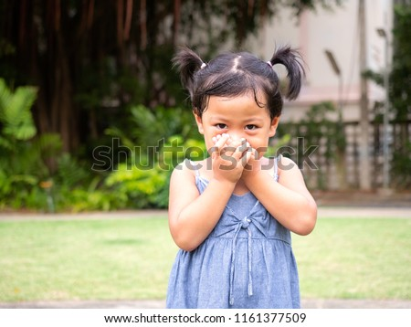 Little cute girl is smiling but used hands to close her mouth and do not say anything.At the park with blurred background. #1161377509