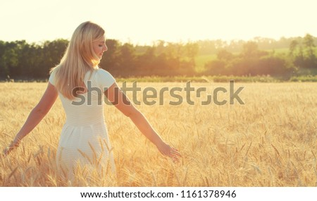 Portrait of a young woman in a wheat field,touches the golden spikelet. #1161378946