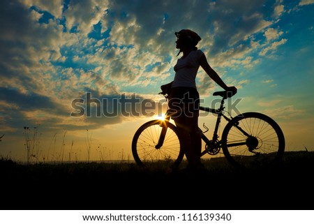 Biker-girl at the sunset on the meadow #116139340