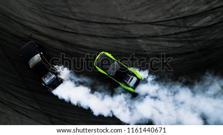 Aerial top view two car drifting battle on asphalt street road race track, Two race car drag view from above, Car turbo drifting, Race drift car with white smoke from burning tire on speed track. #1161440671