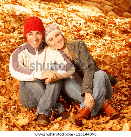 Photo of happy young family spending time together outdoors, cheerful couple sitting on floor covered dry autumnal leaves, man and woman having fun in autumn park, happiness and love concept