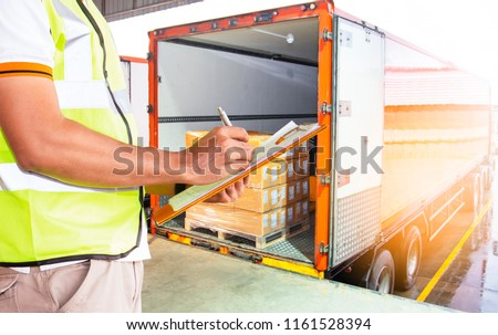 logistics business, warehouse and freight transportation. Worker holding clipboard inspecting control loading cargo shipment into a truck. #1161528394