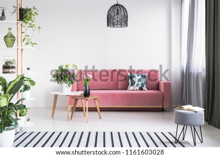 Open book on a gray stool and flowers on wooden tables in cozy living room interior with a pink sofa and striped rug. Real photo #1161603028