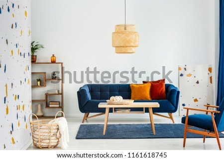 Lamp above wooden table in colorful living room interior with armchair and blue sofa. Real photo #1161618745