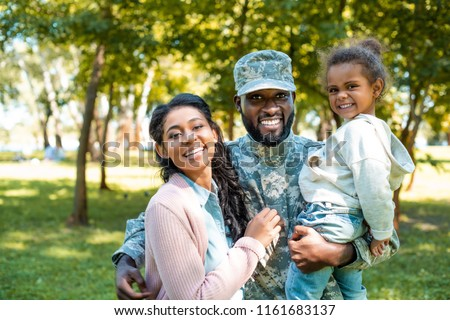 happy african american soldier in military uniform looking at camera with family in park Royalty-Free Stock Photo #1161683137