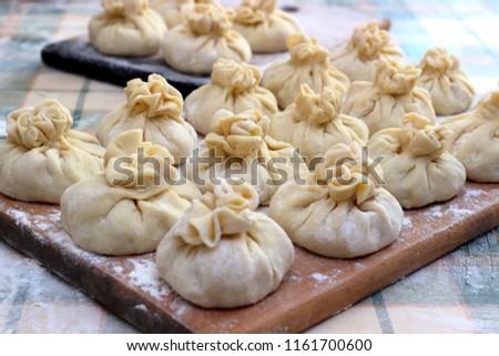 Homemade delicious raw manti (turkish ravioli) from dough on a board sprinkled with flour. Preparation of Manti. Manti, Mantu or Manty Momos, Jiaozi, Dyushbara, Sikkim, Darjeeling,  Mandu, Manti, Pier #1161700600