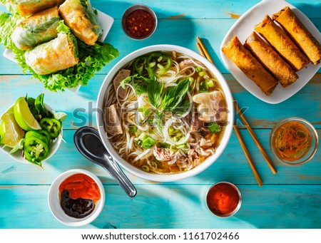 vietnamese beef pho bo soup in bowl on table top with spring rolls and appetizers Royalty-Free Stock Photo #1161702466