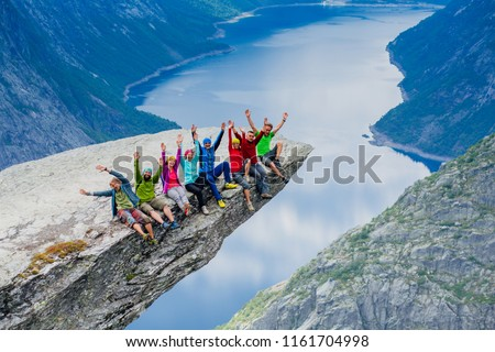 Happy young sportive people group of eight in bright colorful sportswear sitting with hands up and enjoy in Trolltinga Norway mountain. Full body portrait #1161704998