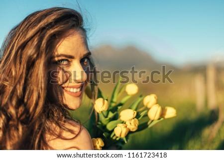 Beautiful brunette women in field with yellow tulip flowers #1161723418