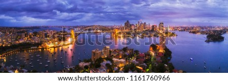 Dark blue sunset over Sydney city on Sydney harbour shores from North to city CBD connected by Harbour bridge in elevated aerial wide panoramic view. #1161760966