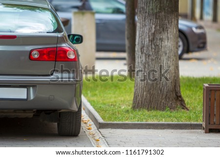 Vehicles design and parking problems concept. Close up back view, stop lights, mirror and trunk details of new shiny luxurious silver car parked on sunny pavement at big trees on blurred background. #1161791302