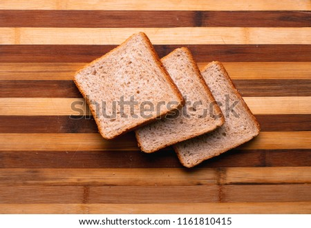 Fresh bread slice and cutting knife on rustic table #1161810415
